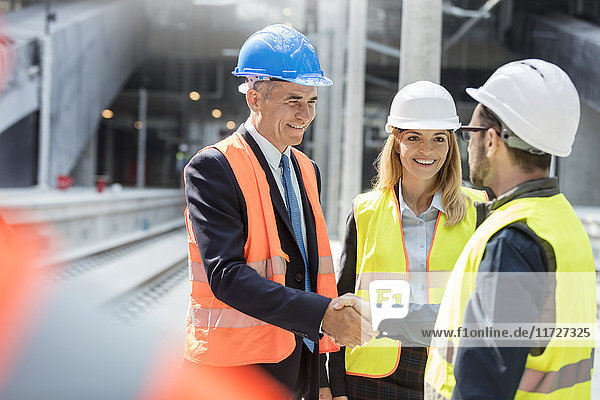 Businessman and engineer handshaking at construction site