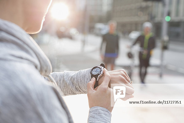 Läuferin beim Prüfen einer intelligenten Uhr in der Stadt