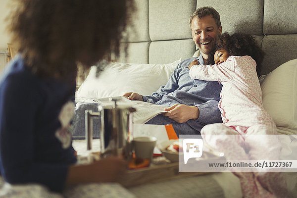 Multi-ethnic daughter hugging father reading newspaper on bed