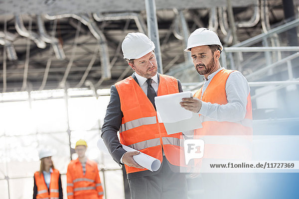 Male engineers with blueprints and clipboard discussing paperwork at construction site