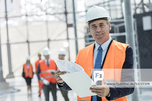 Portrait smiling businessman with clipboard at construction site