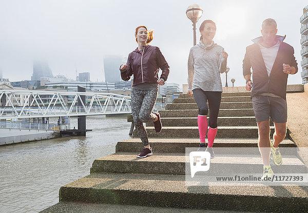 Läufer  die die Treppe entlang der sonnigen städtischen Uferpromenade hinunterlaufen