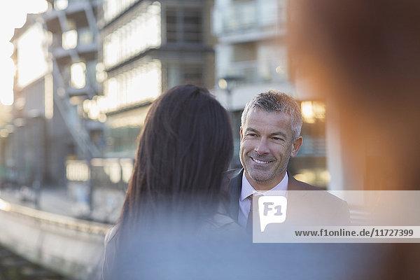 Lächelnder Geschäftsmann  der der Geschäftsfrau in der Stadt zuhört.