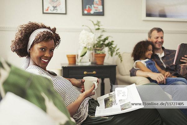 Portrait lächelnde Frau entspannt mit Tee und Magazin auf Sofa
