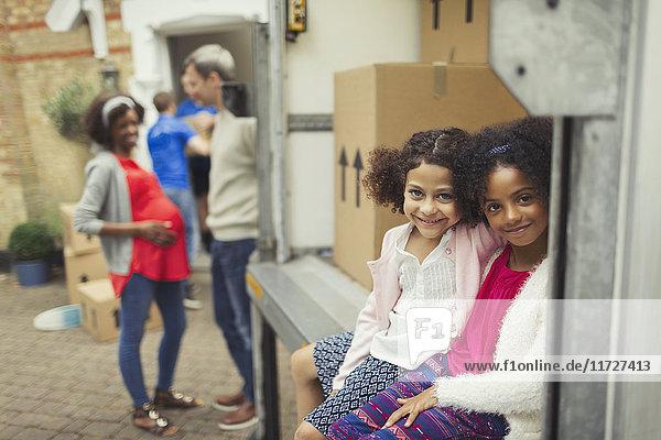 Portrait lächelnde Schwestern sitzen im Umzugswagen vor dem neuen Haus