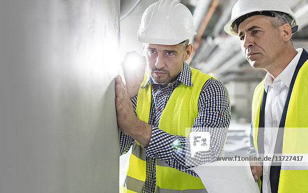 Male engineer with flashlight examining underground wall at construction site