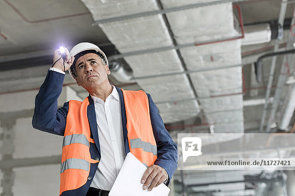 Foreman with flashlight at construction worker