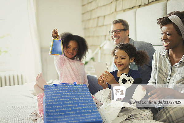 Multi-ethnische Familie Eröffnung Geburtstagsgeschenk auf dem Bett