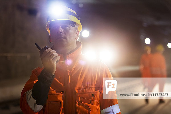Male foreman with headlamp using walkie-talkie at dark construction site