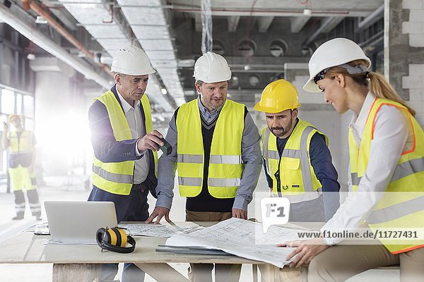 Engineers reviewing blueprints at construction site