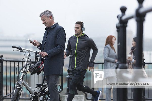 Businessman with bicycle texting with cell phone and male runner on urban ramp