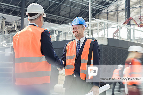 Male engineers handshaking at construction site