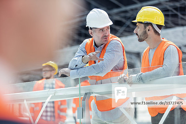 Male foreman and construction worker talking at construction site