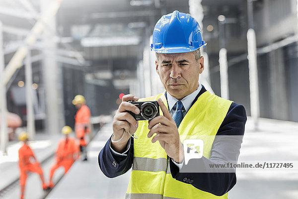 Businessman using digital camera at construction site