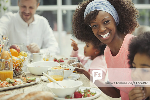 Portrait smiling mother eating breakfast with young family at table