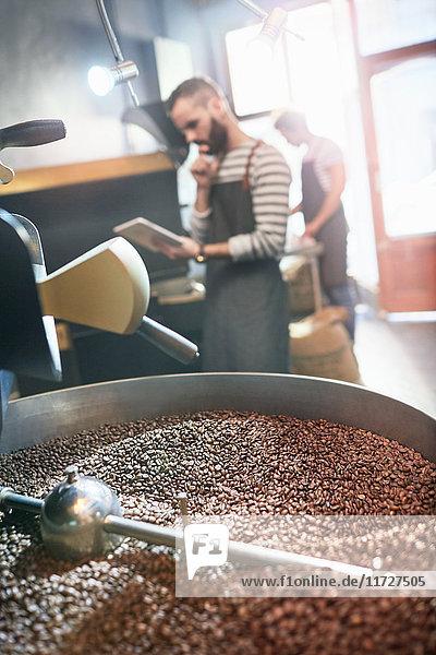 Kaffeeröster mit digitaler Tablette hinter dem Rösten von Kaffeebohnen