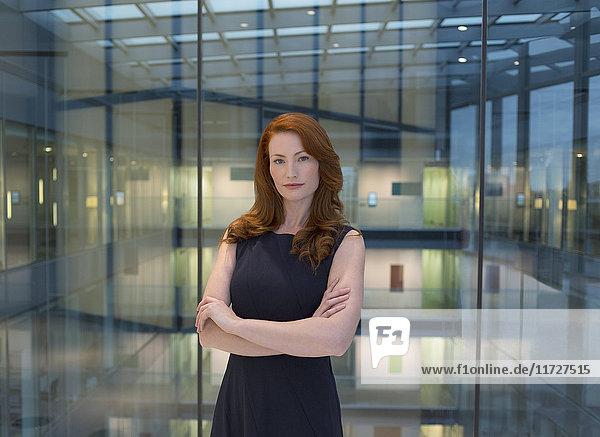 Portrait selbstbewusste Geschäftsfrau mit roten Haaren im modernen Büroatrium