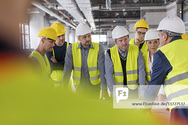 Foreman talking to engineers and construction workers at construction site
