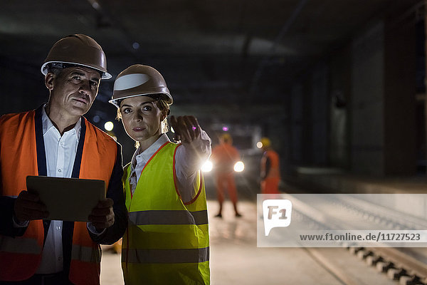 Foreman and engineer with digital tablet talking on dark tracks at underground construction site