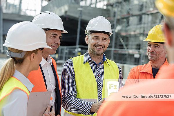 Smiling engineers and construction workers meeting at construction site