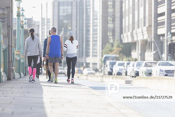 Läufer  die auf dem sonnigen städtischen Bürgersteig laufen