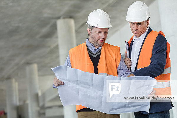 Male engineers examining underground blueprints at construction site