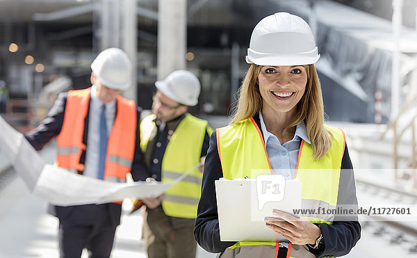 Portrait smiling female engineer with clipboard at construction site
