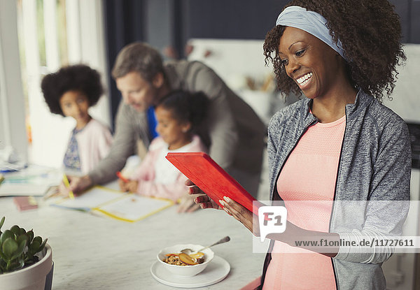 Smiling mother using digital tablet and eating breakfast in kitchen with young family