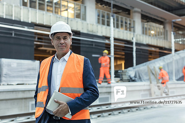 Portrait confident engineer with digital tablet at construction site
