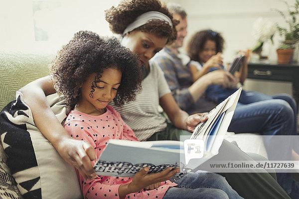 Eltern lesen Bücher mit Töchtern auf dem Wohnzimmersofa