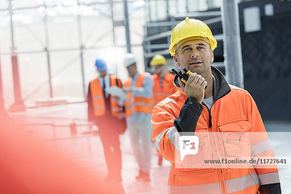 Male foreman using walkie-talkie at construction site