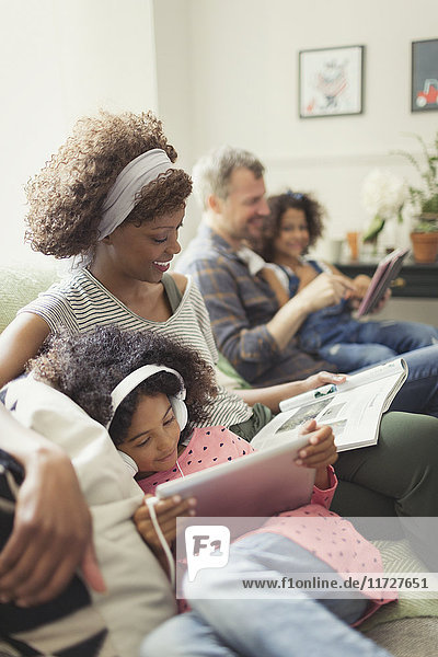 Multi-ethnic young family relaxing  reading and using digital tablet on sofa