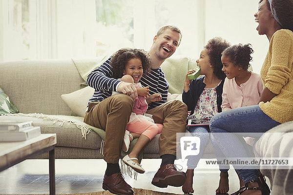 Multi-ethnische junge Familie lacht auf dem Sofa