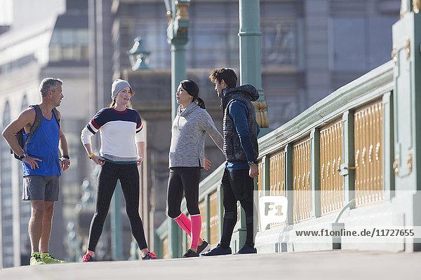 Läufer sprechen und strecken sich auf dem sonnigen städtischen Bürgersteig.