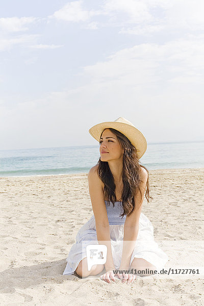 Junge Frau mit Hut kniend am Strand
