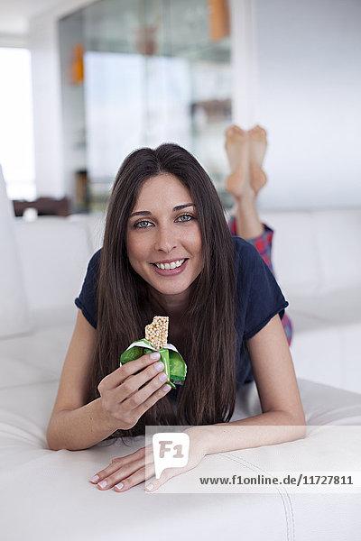 Hübsche Frau mit Müsliriegel auf dem Sofa