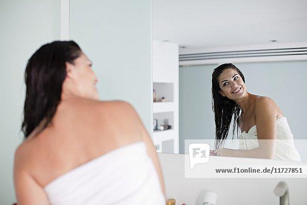 Brünette Frau bürstet ihr Haar vor dem Spiegel