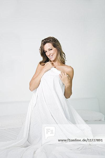 Provokante Frau im Bett mit Bettwäsche und lächelndem Blick auf die Kamera