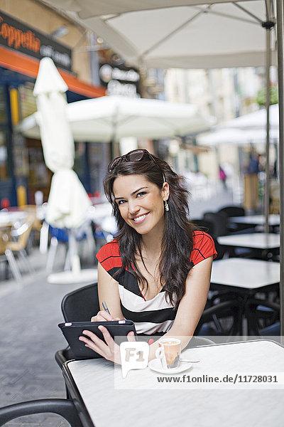 Porträt einer Frau mit Tablette bei einem Kaffee im Freien mit Blick auf die Kamera