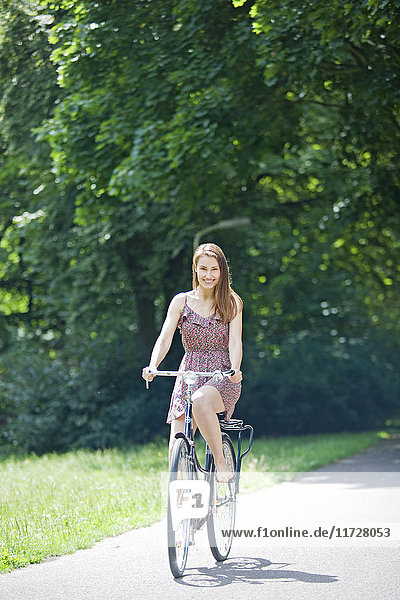Pretty woman riding a bicycle in park