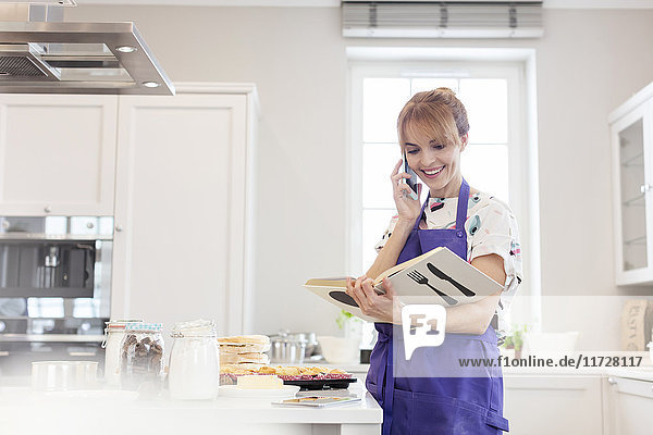 Female caterer with cookbook baking  talking on cell phone in kitchen