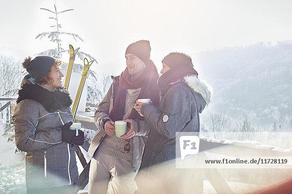 Skifahrerfreunde unterhalten sich  trinken Kaffee und heißen Kakao Apres-Ski