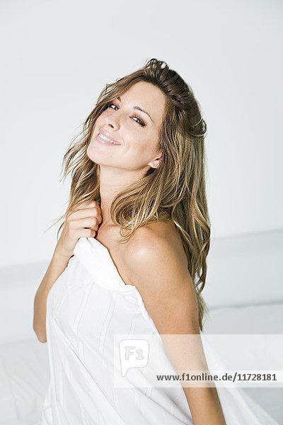 Porträt einer schönen Frau  die ihren Körper mit Laken bedeckt und vor der Kamera lächelt.