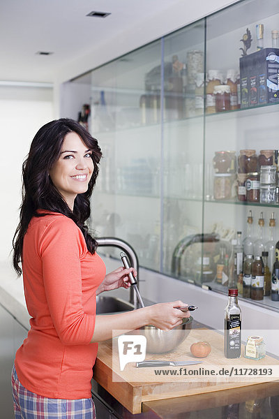 Pretty brunette woman preparing a salad in the kitchen smiling at camera