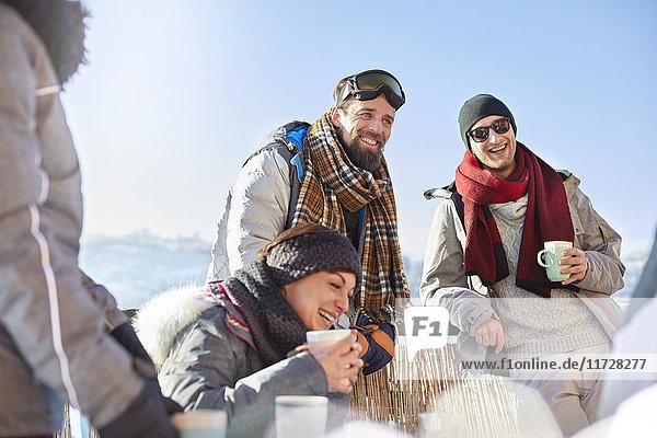 Lächelnde Skifahrerfreunde trinken Kaffee und heißen Kakao außerhalb des Apres-Skis