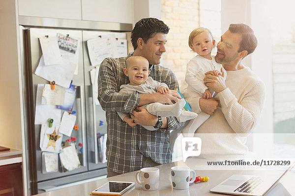 Männliche schwule Eltern halten Babysöhne in der Küche.