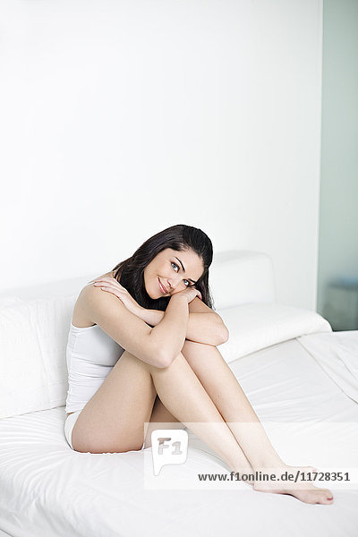 Porträt einer hübschen Frau im Bett lächelnd vor der Kamera