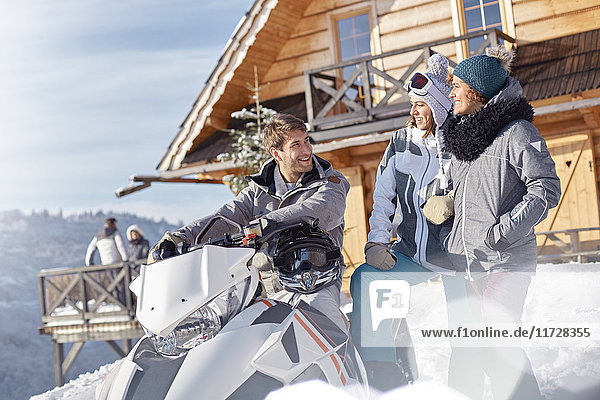 Friends with snowmobile outside sunny cabin