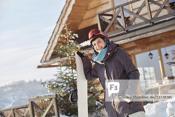 Lächelnde Snowboarderin mit Snowboard außerhalb der sonnigen Hütte