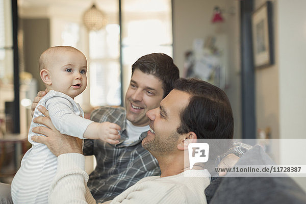Male gay parents holding cute baby son on sofa